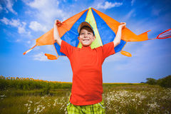 Kid flies a kite into the blue sky Stock Images