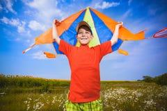 Kid flies a kite into the blue sky. Happy Little boy flies a kite into the blue sky Stock Images