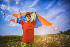 Kid flies a kite into the blue sky Royalty Free Stock Images