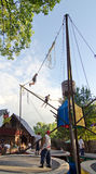 Kid Flinger. Two kids performing acrobatics on a bungi trampoline as workers look on, at the Bristol Renaissance Faire in Wisconsin Stock Images