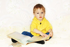 Kid flips through a book. Royalty Free Stock Photos