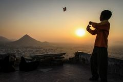 Kid flying his kite at sunset at the Pap Mochani Gayatri Temple, Pushkar, Rajasthan, India. Pushkar is a town bordering the Thar Desert, in the northeastern stock photo