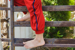 Kid foot climb on the rust iron bar Royalty Free Stock Image