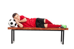 Kid in a football uniform sleeping on bench Stock Images