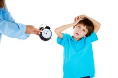 A kid forced to go to bed by mom. Closeup portrait of mom showing kid clock that it is time to go to bed. He doesn't like that. Isolated on white background Stock Images
