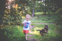 Child and a dog friendship  running in forest
