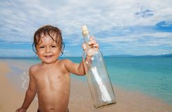 Kid found sos bottle in the sea Royalty Free Stock Photos