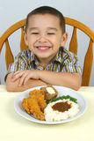 Kid and Fried Chicken. A 4-year-old boy ready to eat his fried chicken dinner with mashed potatoes and trimmings stock photography