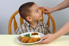 Kid and Fried Chicken. A young boy ready to eat his fried chicken dinner with mashed potatoes, green beans, and a whole wheat dinner roll stock photos