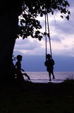 Kid & Friend on Swing Borneo Coast. SE Asia stock photos