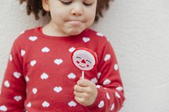 Kid with a fro hair holding a sweet piece of candy. African american little girl holding a Christmas lollipop royalty free stock image