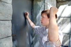 Kid in Front of Closed Door. Kid knock in the Closed Door outdoor Royalty Free Stock Image