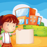 A kid in front of the school with an empty paper Stock Images