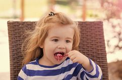 Kid with frozen fruit yogurt, gelato or sorbet. Boy with icecream in outdoor cafe. Food, refreshing dessert eating concept. Summer, vacation, holidays. Child Stock Image