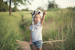 Kid in funny animal hat playing. With wooden toy horse on sunset royalty free stock images