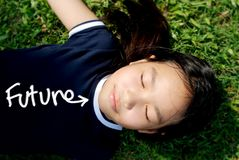 Kid future. Close-up of smiling girl sleep on grass with the word future on her t-shirt royalty free stock images