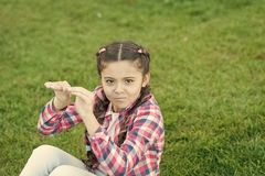Kid gadabout. Girl little kid spend leisure outdoors in park. Girl sit on grass in park. Child enjoy spring sunny. Weather while sitting at meadow in park stock images