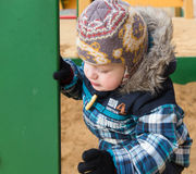 The kid gets on a sandbox side at a playground and looks for a c Royalty Free Stock Images