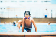 Kid getting out of swimming pool stock photos