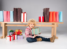 Kid with gift boxes and shopping bags. Happy kid sitting with pile of gift boxes and shopping bags on grey Stock Photography