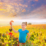 Kid girl in autumn vineyard field holding red grapes bunch. Blond Kid girl in happy autumn vineyard field holding red leaf grapes bunch in hand Royalty Free Stock Images