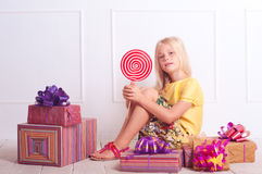 Kid girl with birthday presents. Cute kid girl sitting on floor with presents on white Royalty Free Stock Photography