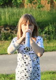 Kid - girl with blowpipe Royalty Free Stock Photos