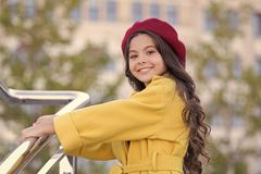 Kid girl bright hat beret. Autumn hat fashion accessory. French trend fall season. Girl walk defocused background. Charming little french style fashionable royalty free stock images