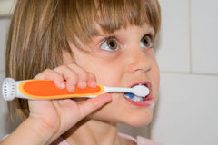 Kid girl brushing teeth in bathroom Royalty Free Stock Photos