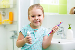 Kid girl brushing teeth in bathroom Stock Photography