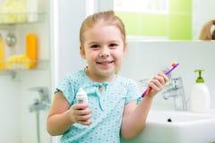 Kid girl brushing teeth in bathroom stock photography