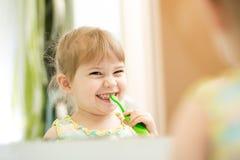Kid girl brushing teeth in bathroom royalty free stock photo