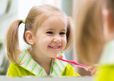 Kid girl brushing teeth in bathroom. Cute child kid girl brushing teeth in bathroom royalty free stock images