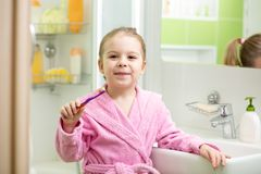 Kid girl brushing teeth in bathroom Royalty Free Stock Photo