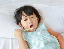 Kid girl brushing teeth on the bed at morning.  stock photos