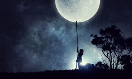 Kid girl catching moon Stock Photography