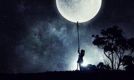 Kid girl catching moon Stock Image