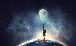 Kid girl catching moon Royalty Free Stock Images