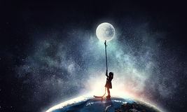 Kid girl catching moon Stock Photo