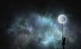 Kid girl catching moon. Silhouette of kid girl pulling full moon with rope stock photo