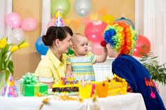 Baby girl celebrating first birthday with parents and clown Stock Photos