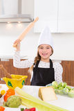 Kid girl chef on countertop funny gesture with roller knead Stock Photo