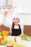 Kid girl chef on countertop funny gesture with roller knead Royalty Free Stock Image