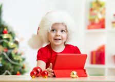 Kid girl in christmas hat with tablet pc Stock Photo