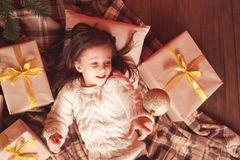 Kid girl with christmas presents under chrismas tree Royalty Free Stock Image