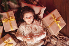 Kid girl with christmas presents under chrismas tree Royalty Free Stock Images