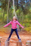 Kid girl climbing tree trunks with open arms. Having fun in the pine forest stock photo