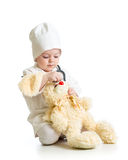 Kid girl with clothes of doctor playing with plush toy Stock Images