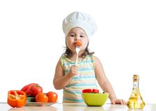 Kid girl in cook hat eating vegetables Royalty Free Stock Photos