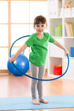 Kid girl doing gymnastic with hoop in children room at home Stock Photography